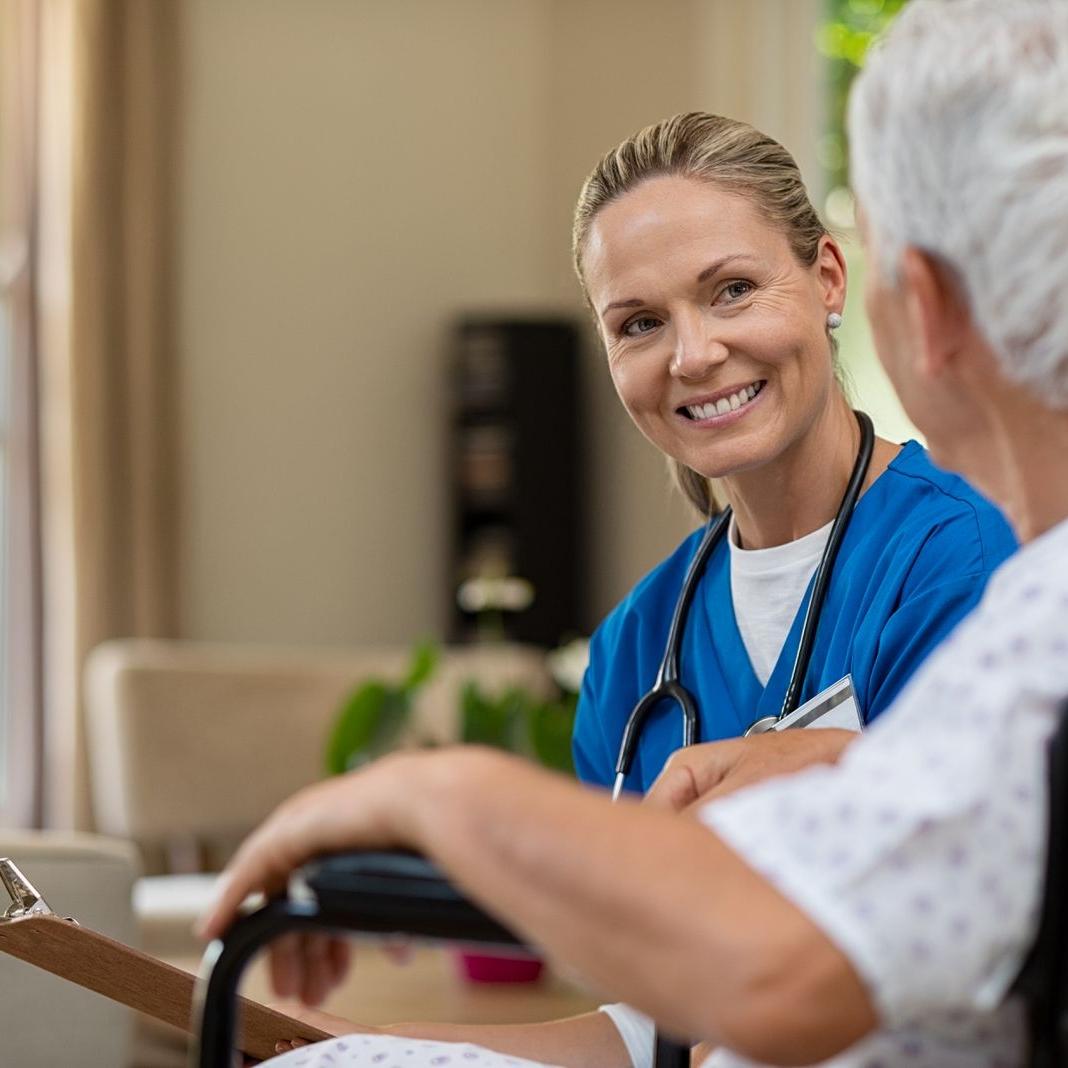 friendly-nurse-talking-to-senior-patient-Q58Y9GB-1600-80